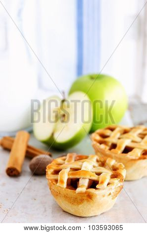 Lattice fruit pies with fresh apples, raw nutmeg and cinnamon in the background
