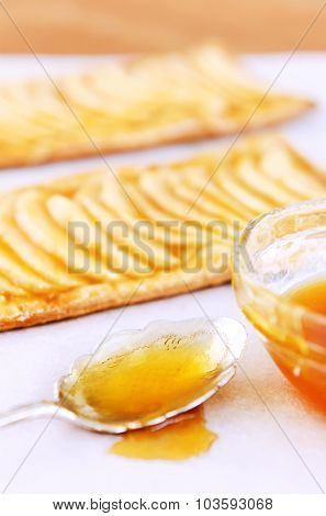 Vintage spoon dripping with apricot glaze and baked pastries in the background