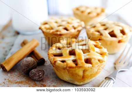 Small lattice apple pies with raw spices like cinnamon and nutmeg, presented on a rustic wooden board