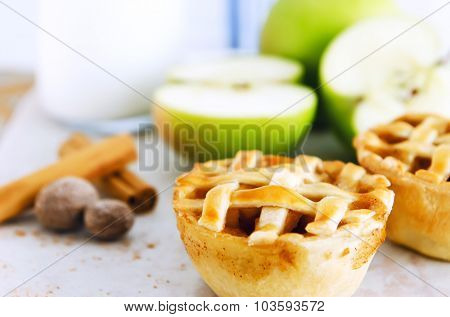 Baked apple pies with a lattice top, presented with fresh apples and raw spices in the background