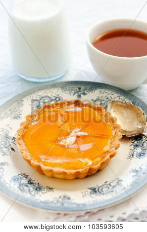 Beautiful caramelised tart, cracked to show the custard within served on a vintage plate