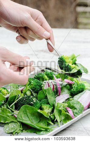 Tossing and serving a healthy green salad with spinach, broccoli and seeds