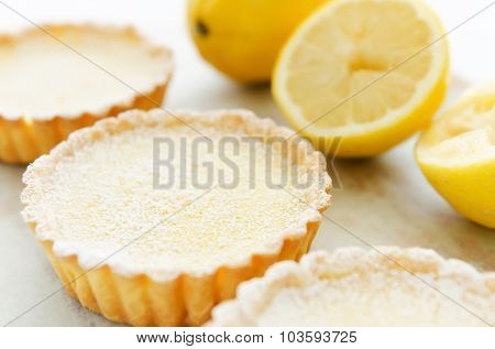 Three lemon tarts dusted with icing sugar, decorated with lemons in the background