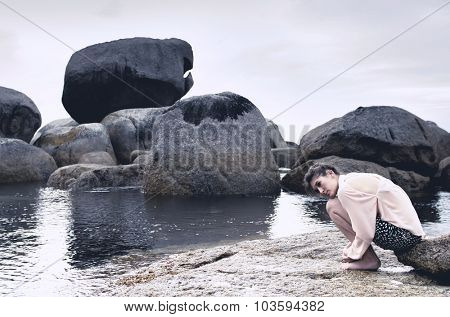Lonely isolated woman huddling on rocks by the seaside