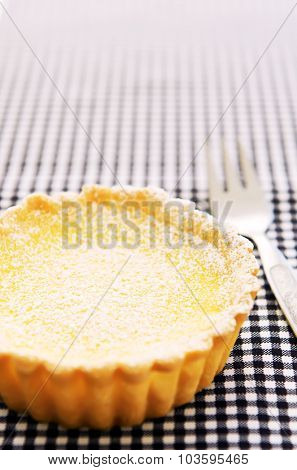 Yellow custard tart sprinkled with icing sugar on a blue and white checkered cloth with copyspace
