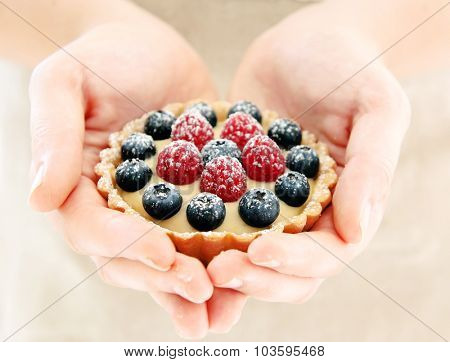 Female hands showing a fresh fruit tart, her hands forming a heart shape
