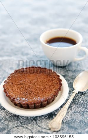 Teatime snack of a chocolate tart and coffee