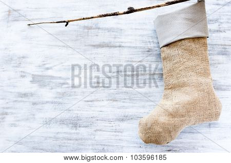 Christmas stocking made with burlap hessian hanging on a branch twig on a rustic farmyard background
