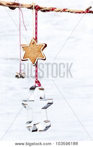 Christmas background with xmas decoration gingerbread man cookie cutter, star and bell hanging off a branch