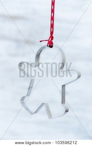 Gingerbread man cookie cutter suspended with red ribbon, christmas xmas theme