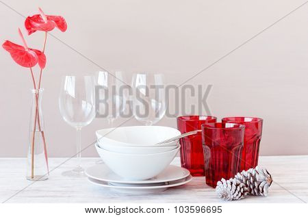 Simple christmas table decoration with red and white crockery and glasses with flower on plain background