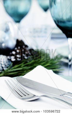Place setting cutlery and blue glasses for christmas with pine cone centerpiece