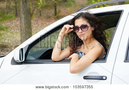 girl driver portrait with sunglasses inside white car