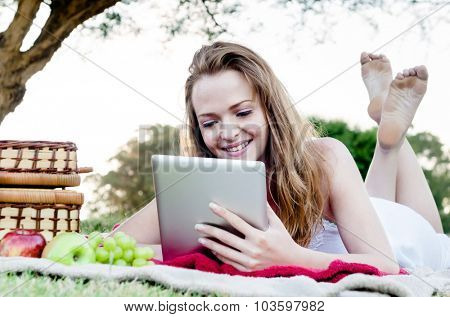 Beautiful young woman with tablet computer in park relaxing and reading with fruit and picnic basket