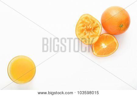Freshly squeezed orange juice with cut oranges on white background