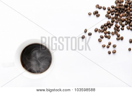 Hot cup of coffee with beans, overhead with plenty of copy space