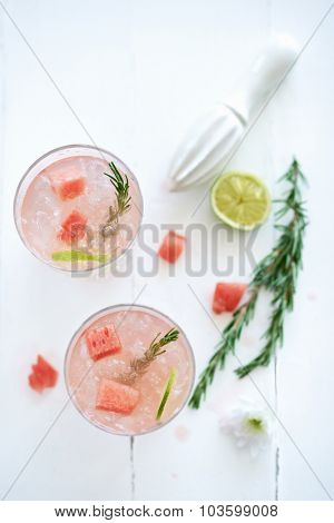 Light pink cocktails mocktail drinks decorated with cut up watermelon and rosemary with a flower and a piece of lime beside it