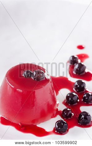 Close up of jelly dessert on white plate with stewed berries and sauce, healthy dessert plenty of copy space