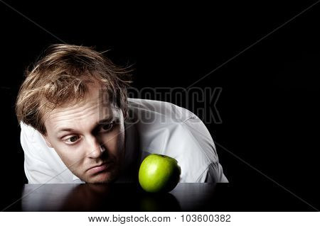 Businessman desaturated, lifeless and unmotivated looking at bright green apple for inspirational idea spark, abstract business concept