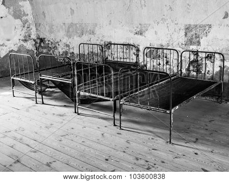 Old rusty beds in abandoned room