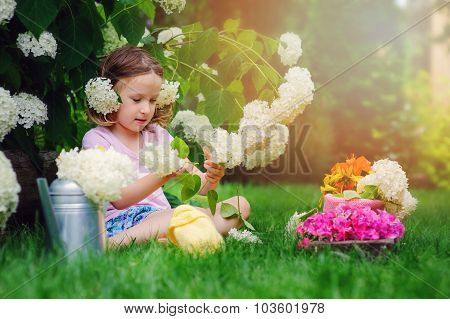 cute child girl playing and making flower bouquet in summer garden