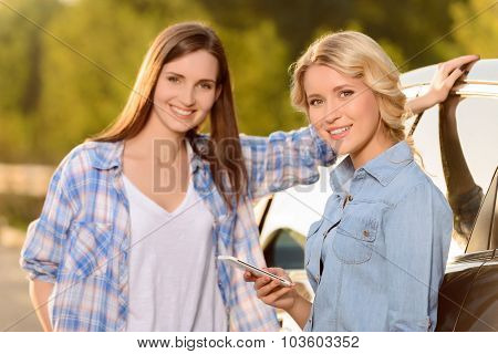 Pleasant girls standing near car