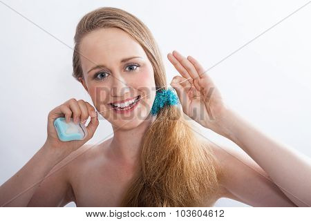 Young Woman Flossing Teeth In White Studio