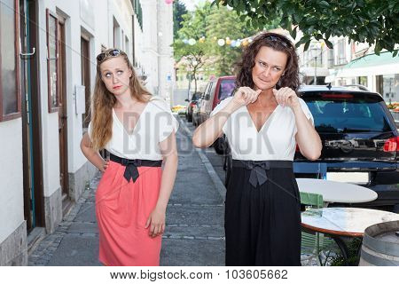 Two Women Walking On Sidewalk Together