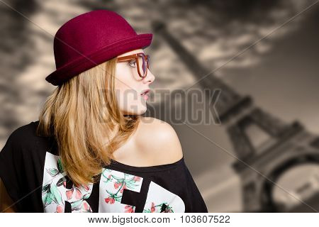 Girl in sunglasses on blurred Eiffel tower background