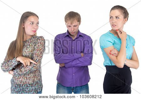 Puzzled Young Man And Two Women