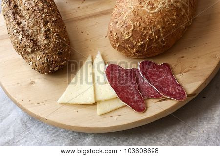 Simple rustic food (white and brown bread, cheese and sausage) on a wooden board