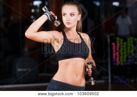 Attractive athletic woman wearing in black top and breeches standing with dumbbells on the sport equipment background in the gym waist up