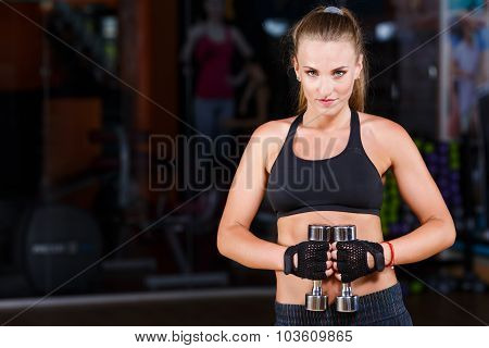 Fitness woman with long hair wearing in black top and breeches standing with dumbbells on the sport equipment background in the gym waist up