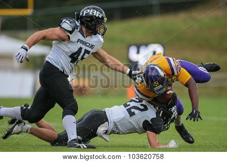 VIENNA, AUSTRIA - JULY 13, 2014: DB Jan Stiegler (#22 Panthers) tackles RB Islaam Amadu (#20 Vikings) during an Austrian football league game.