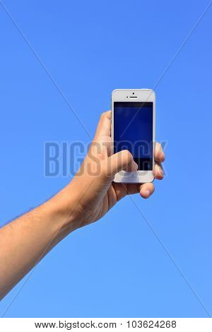 Man's Hand Holding A Phone Against The Sky