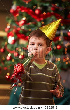 Little Boy Blowing New Year Horn