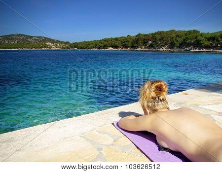 Young Redhead Woman Sunbathing On The Beach By Clear Sea, Croatia Dalmatia