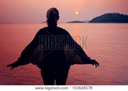 Silhouette Of Young Woman Spreads Her Hands At The Sea With Sunset