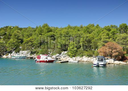 Small Boat Moored To The Rocky Coast Of The Sea Bay, Croatia Dalmatia