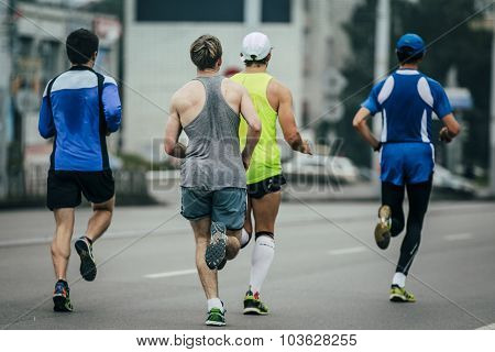 group of young runners running through streets of city