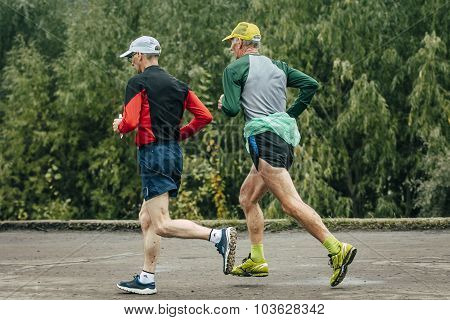 two elderly athlete run along river