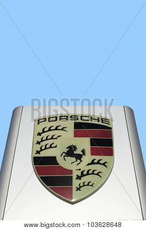 Porsche logo in front of a car dealer