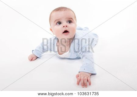 Baby In The Body Lying On His Stomach On A White Background And Looking Up At The Camera