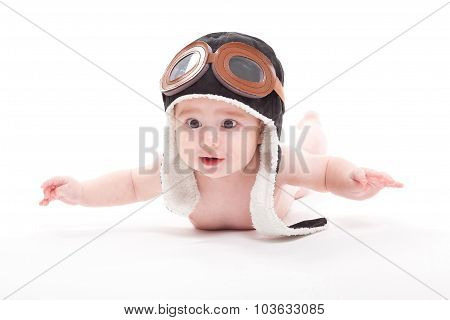 Naked cute smiling baby in the cap of the pilot is flying on a white background