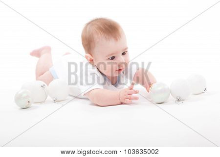 Baby On A White Background Playing With Christmas Toys