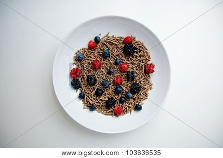 Muesli With Berries In White Dish On Blank White Table Top View