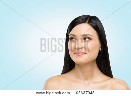 A Portrait Of A Smiling Brunette Lady Who Is Looking At Something On The Right Side. Light Blue Back