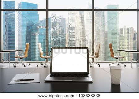 A Workplace In A Modern Panoramic Office In Singapore. A Laptop With White Screen, Notepad And A Cof