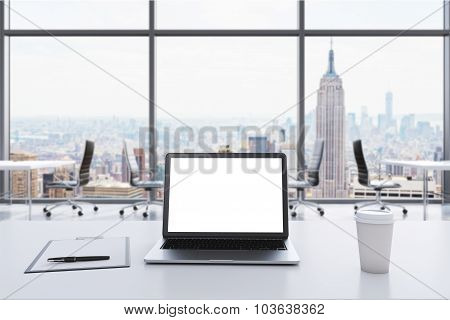 A Workplace In A Modern Panoramic Office In Manhattan, New York. A Laptop With White Screen, Notepad