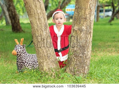 Asian Baby Boy In Santa Claus Suit Is Playing With Reindeer Doll At Outdoor